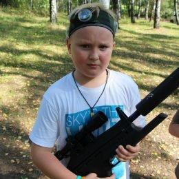 Berniukas miške pozuoja su Laser Tag įranga