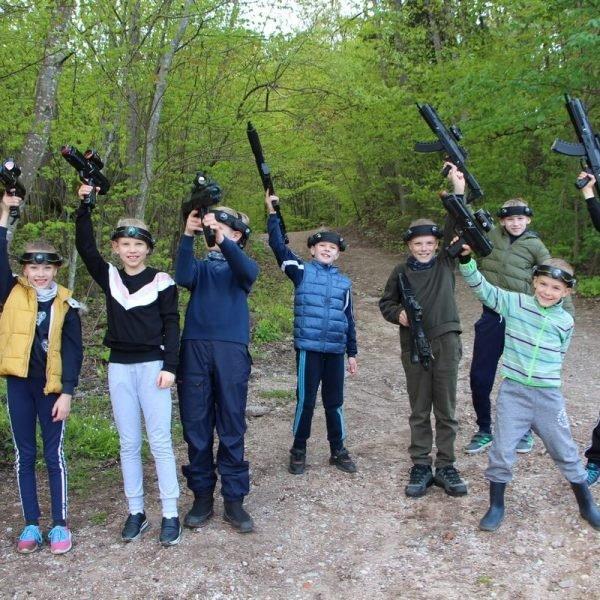 Laser Tag žaidimui gamtoje vaikų būrys pasiruošęs - tageriai iškelti, veiduose šypsenos